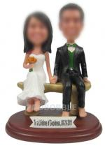 Custom wedding cake topper bobbleheads sitting on bench